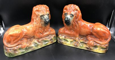 A pair of large Staffordshire pottery lions with glass eyes. 25cms h x 33cms w x14.5cms d.