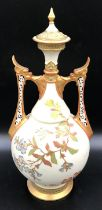 A Royal Worcester lidded vase with floral decoration and pierced dragon headed handles. 41cms.