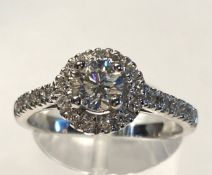 A STUNNING CONTEMPORARY 18CT WHITE GOLD DIAMOND HALO RING, with a centre diamond .60cts, total