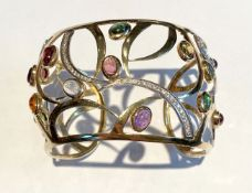 A 14CT YELLOW GOLD OPEN WORK CONTEMPORARY DESIGN BANGLE, mounted with 15 cabochon amethyst,