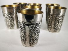 A SET OF SEVEN SILVER TUMBLERS, marked 800, continental silver, each decorated with fruiting vine
