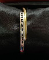 AN ITALIAN 18CT YELLOW AND WHITE GOLD SAPPHIRE AND DIAMOND BANGLE, in a hinge design, with 8