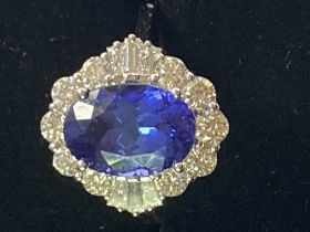 AN 18CT WHITE GOLD ART DECO STYLE TANZANITE AND DIAMOND CLUSTER RING, the superb oval shaped