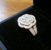 A STUNNING 18CT WHITE GOLD DIAMOND CLUSTER RING, in the form of a flower, main stone, brilliant cut,