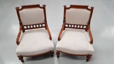 A PAIR OF GOOD QUALITY WALNUT LOW RISE CHAIRS / BEDROOM CHAIRS, with down swept scroll shaped elbow