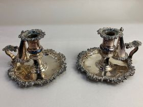 A pair of 19th century silver plated chamber sticks, with snuffers, the borders of embossed floral