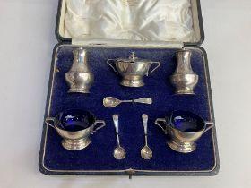 A cased George V silver five piece cruet set, maker Josiah Williams & Co, London 1928, with blue