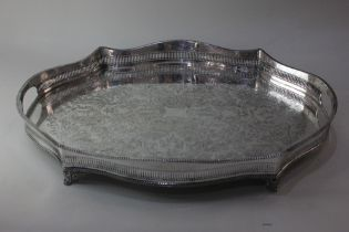 A silver plated serving tray with serpentine shaped pierced raised border and scroll and foliate