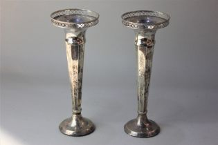 A pair of George V silver vases with pierced rims on facetted tapered stems and loaded circular