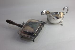 A silver plated sauce boat with flying scroll handle on three paw feet, and a chestnut warming pan