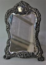 A Victorian silver mounted dressing table mirror embossed scroll shaped frame surmounted with vacant