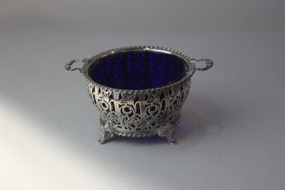 A George VI pierced silver two handled circular dish with blue glass liner on four scroll feet,