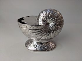 A silver plated nautilus shell shaped spoon warmer with hinged lid on floral engraved oval base,