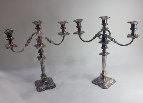 A pair of silver plated three-light candelabra with urn shaped sconces and detachable drip trays