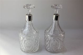 A pair of George V silver mounted cut glass decanters cylindrical shape with tapered necks and