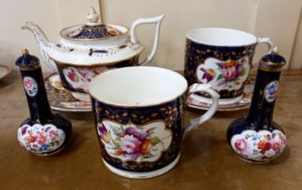 A collection of 19th century English porcelain painted with panels of flowers on a blue and gilt