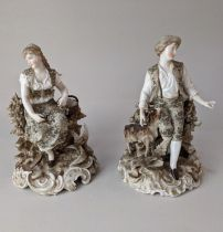 A pair of Rudolstadt Volkstedt porcelain figures of a seated man and women, on scroll bases, with