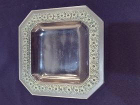 A Rene Lalique 'Paquerettes' square canted glass dish moulded with flowers highlighted in green,