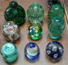 Nine various large glass paperweights including green bubble glass examples