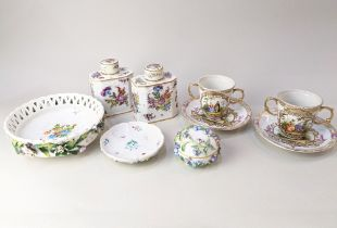 A pair of Augustus Rex style porcelain chocolate cups and saucers (missing covers), decorated with