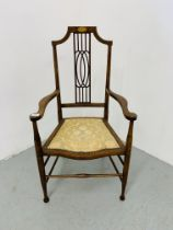 AN EDWARDIAN MAHOGANY STRUNG BACK ELBOW CHAIR WITH UPHOLSTERED SEAT
