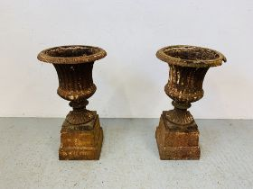 A PAIR OF CAST IRON TULIP SHAPE GARDEN URNS ON STANDS A/F CONDITION - OVERALL HEIGHT 68CM.
