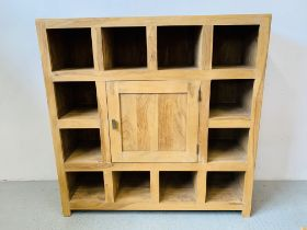 A HARDWOOD ACACIA PIGEON HOLE DISPLAY CABINET WITH CENTRAL CUPBOARD - W 135CM. D 45CM. H 135CM.