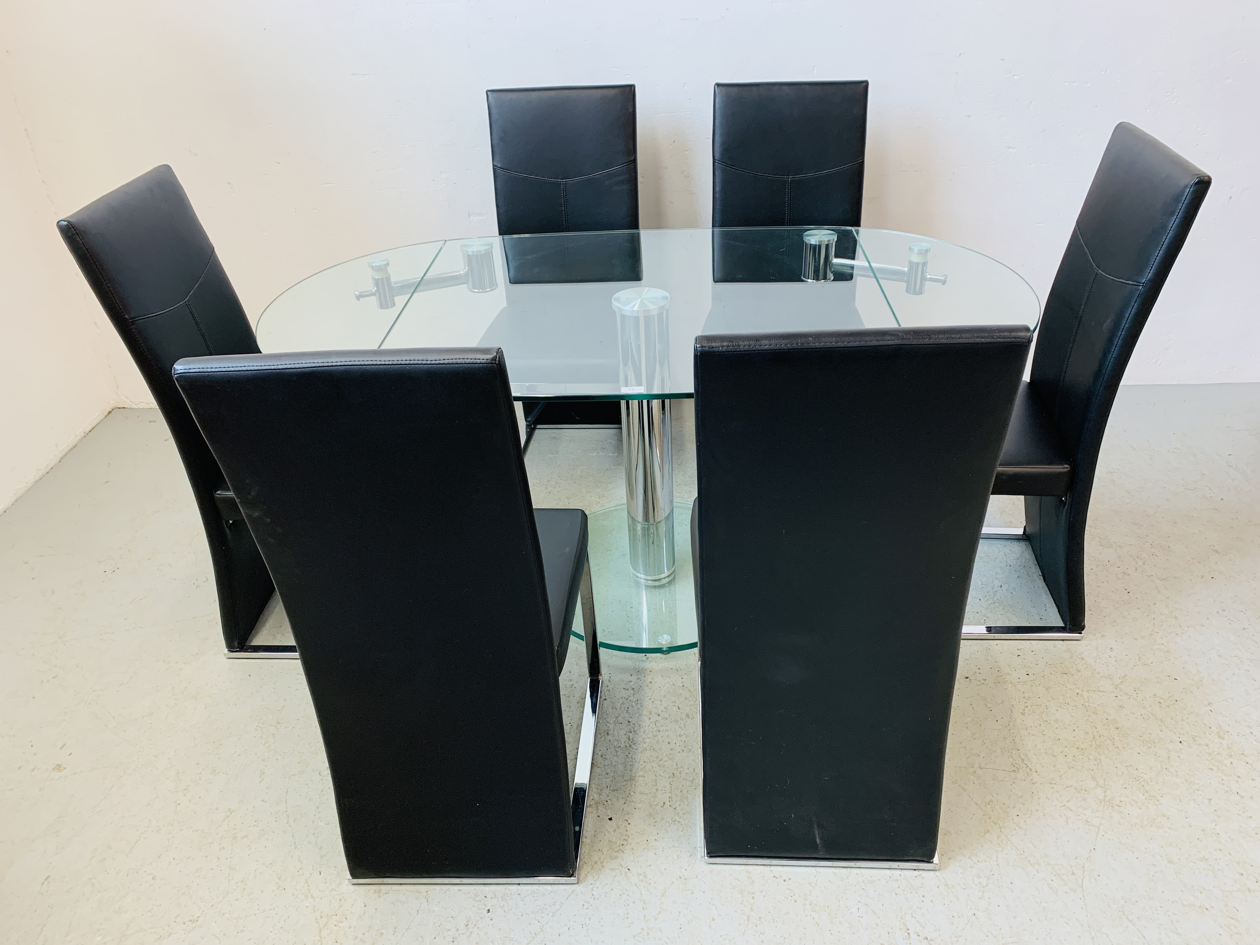 A DESIGNER GLASS AND CHROME PEDESTAL DINING TABLE WITH SET OF SIX CHROME FRAMED LEATHERETTE DINING