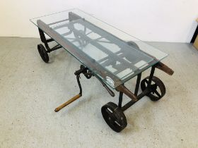 A GLASS TOP EXTENDING COFFEE TABLE CONVERTED FROM AN ANTIQUE COOKS RATCHET ACTION SACK BARROW