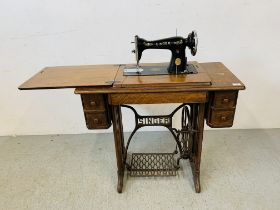 A SINGER SEWING MACHINE IN FITTED WORK TABLE WITH ACCESSORIES