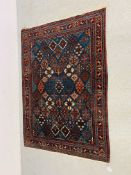 AN EASTERN RED / BLUE PATTERNED RUG - 148CM X 108CM.