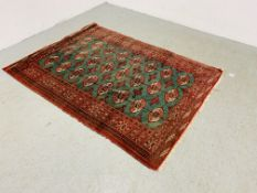 AN EASTERN RED / GREEN PATTERNED RUG 180CM X 130CM.