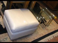 A nest of glass tables, together with a cream pouf