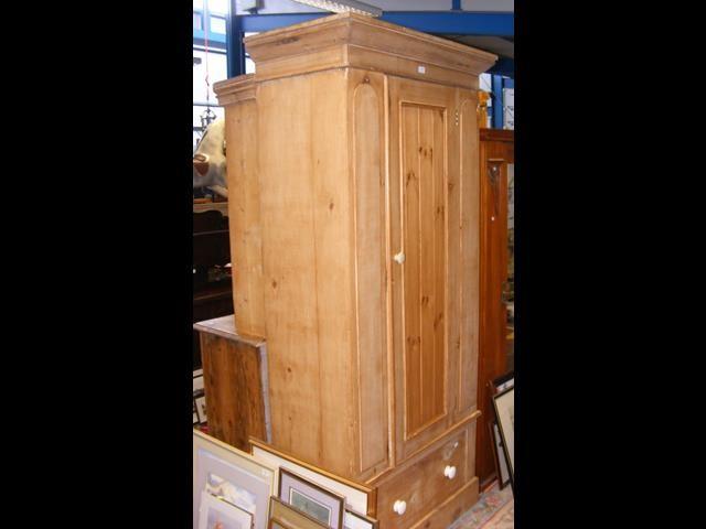 A stripped pine wardrobe with single swing door an