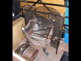 A wrought iron fire basket with tools, copper coal