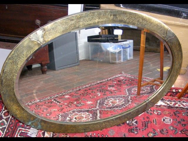 A oval wall mirror with hammered metal frame