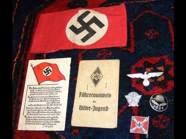 A Nazi armband together with various badges