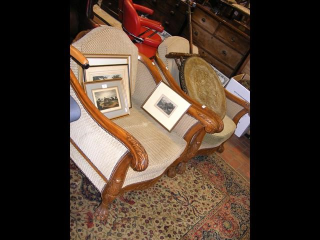 A pair of antique style easy chairs with carved ar