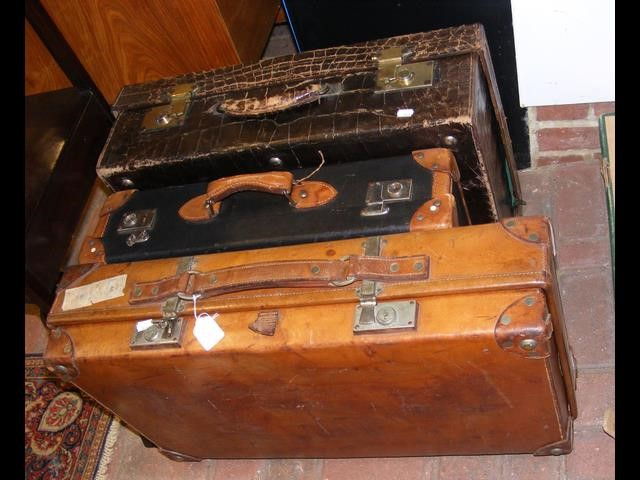 A vintage leather suitcase, together with two othe
