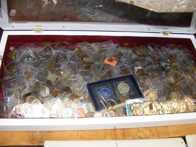 A mixed lot of UK and other coinage in display cas