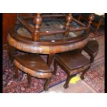 An oriental oval table with carved scene below gla
