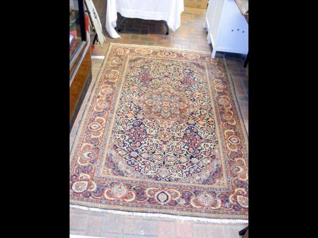 An antique Middle Eastern carpet with geometric bo