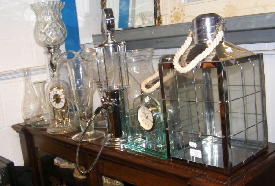 A mantel clock, drink dispenser, glass vases