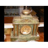 A green onyx mantel clock with gilt columns and tw