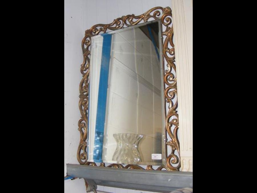 A bevelled wall mirror with scroll surround