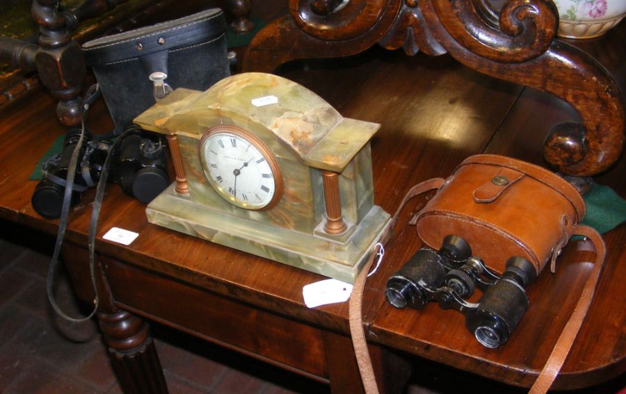 A mantel clock together with two pairs of binocula