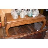 A Chinese low occasional table with carved ends -
