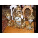 A gilt German mantel clock with matching garniture