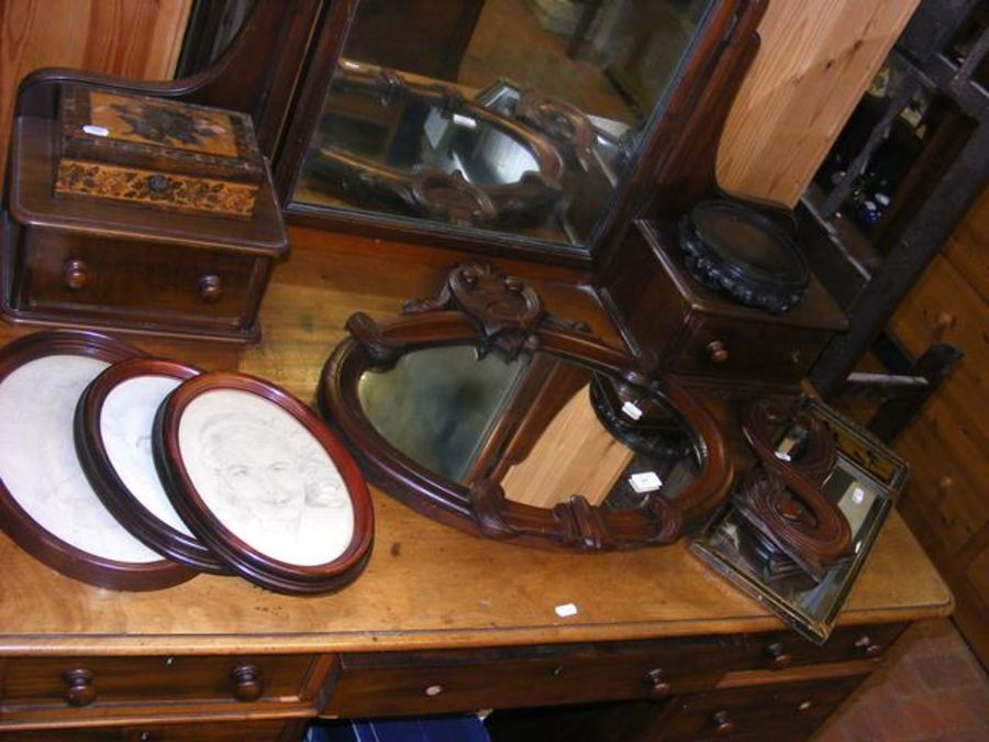 An oval mirror in carved wooden frame together wit
