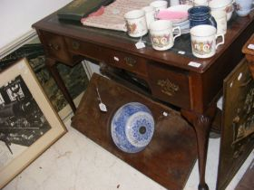 A writing desk with green leather top and three dr